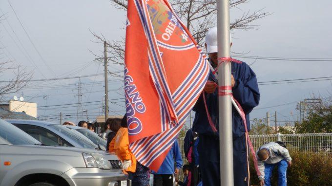 スポコミ東北の柳見沢さんがパルセイロの旗を掲げています
