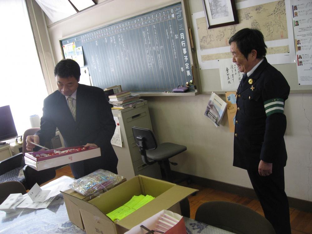 マスコット人形をみて思わず笑顔の青木正治校長と金井さん