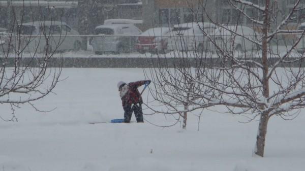 南側の市道までの雪をかく生徒